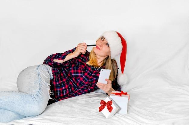 Prezent świąteczny. figlarnie uśmiechnięta kobieta z prezentem