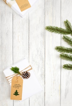 Prezent świąteczny i dekoracja liści sosny na białym drewnianym stole