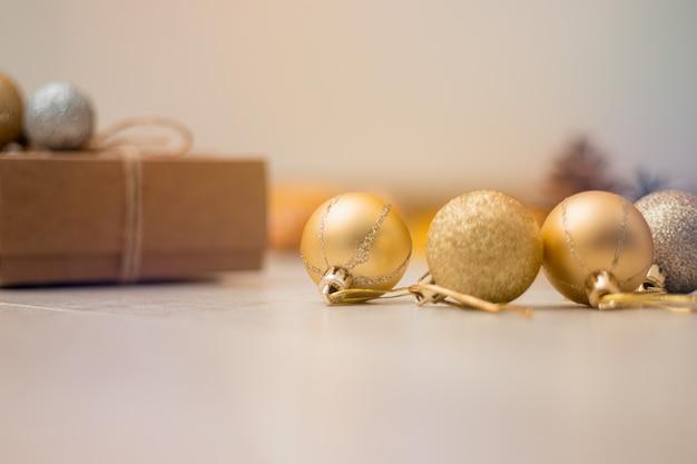 Prezent świąteczny, kule dekoracji i szyszki na stole.