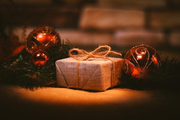 Prezent świąteczny na tle ozdób choinkowych.zdjęcie z miejscem na kopię