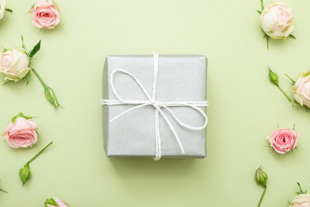 Prezent świąteczny. srebrne pudełko na zielonym stole. różne dekoracje na granicy róż.