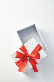 Prezent świąteczny w białym papierze do pakowania i czerwonymi wstążkami