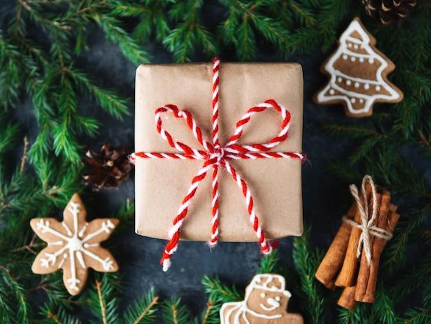 Prezent świąteczny w czapce mikołaja na świątecznym stole z domowymi ciasteczkami imbirowymi i laskami cynamonu oraz gałęziami choinki