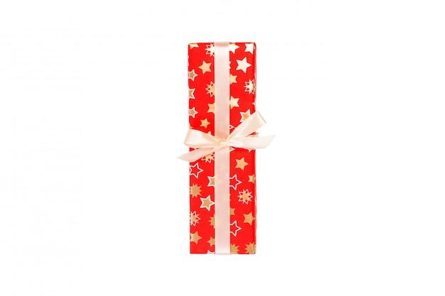 Prezent świąteczny w czerwonym papierze ze złotą wstążką
