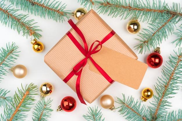 Prezent świąteczny w otoczeniu sosnowych gałęzi i mini bombek