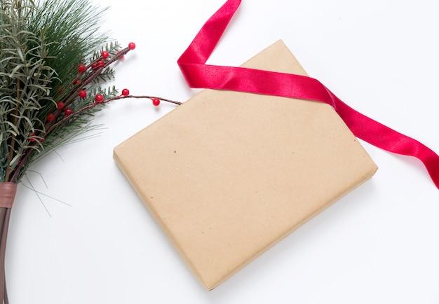 Prezent świąteczny w papierze rzemieślniczym z czerwoną wstążką