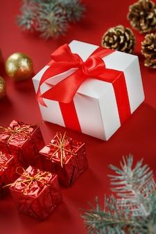 Prezent świąteczny w postaci białego pudełka z czerwoną kokardką wokół ozdób choinkowych