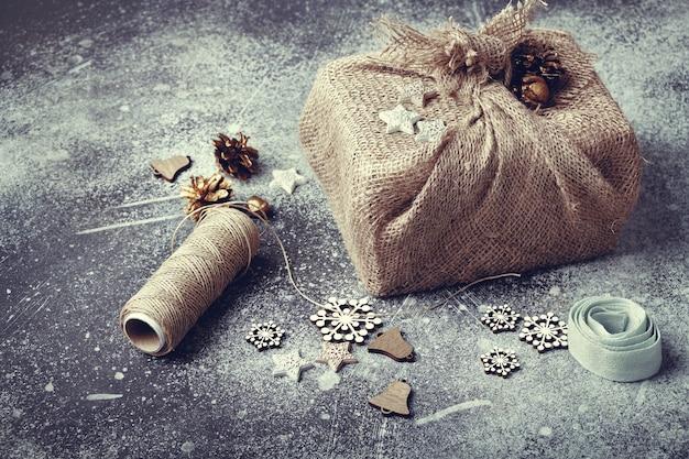 Prezent świąteczny zawinięty w płótno. lniany sznurek i drewniane ozdoby