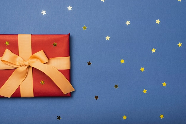 Prezent świąteczny ze wstążką i złotymi gwiazdami