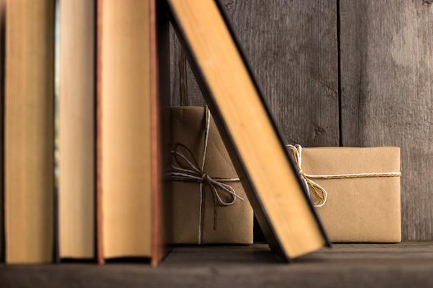 Prezent ukryty na drewnianej półce za książkami.