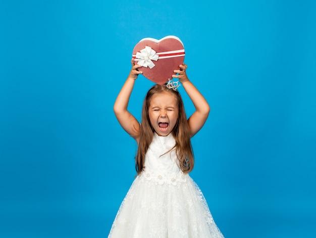 Prezent urodzinowy dla dzieci. pudełko na niespodziankę i prezent. mała dziewczynka trzyma pudełko z prezentem.