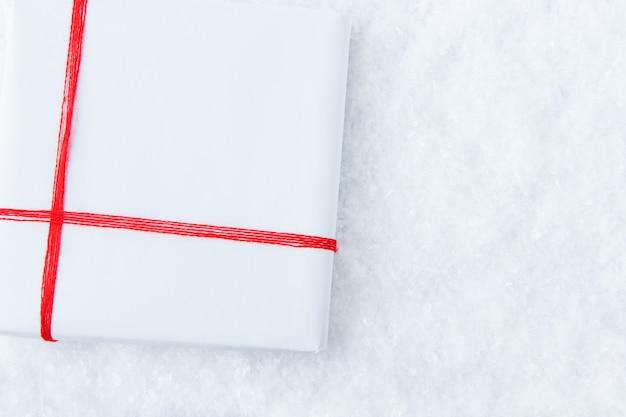 Prezent w białym kolorze przewiązany czerwoną wstążką leży na śniegu widok z góry święta bożego narodzenia