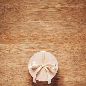 Prezent w drewnianym pudełku z jasnokremową kokardką na dębowym stole