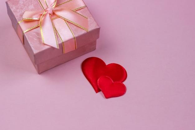 Prezent w pięknym pudełku i czerwone serca na różowym tle.