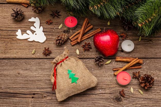 Prezent w worku, drzewo noworoczne, jabłko, świece, przyprawy, jeleń, szyszki. dekoracje przyrodnicze, zabytkowe drewniane deski