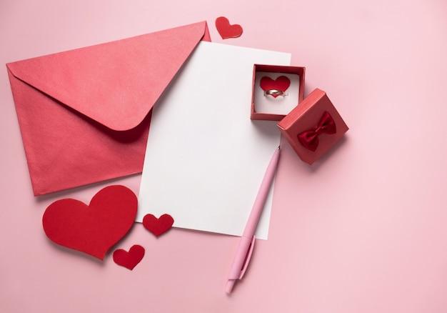 Prezent walentynkowy w pudełku, liście i kopercie z kopią miejsca na różowym tle. pierścionek do oświadczyn, leżący na płasko. zaproszenie na ślub, wyznanie miłości. makieta, widok z góry