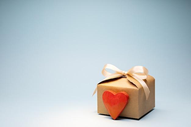 Prezent walentynkowy z kremową kokardką ze wstążki w pudełku kartonowym z czerwonym drewnianym sercem