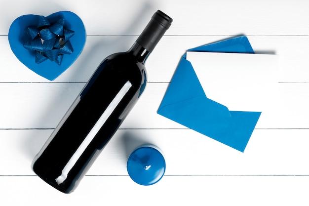 Prezent, wino, list, świeca na białej powierzchni drewnianych.
