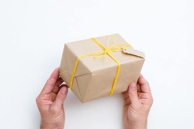 Prezent wykonany ręcznie. serdeczne gratulacje i nagroda dla wyjątkowej osoby. ręce trzymając prezent zawinięty w papier i przewiązany żółtym sznurkiem.