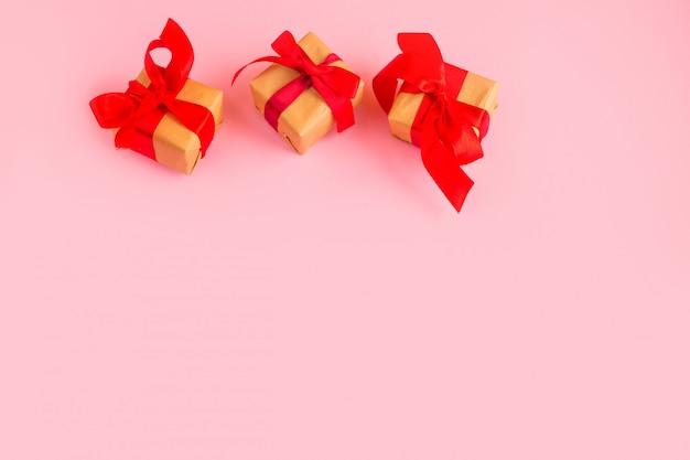 Prezent z czerwoną kokardą na różowym tle z tittle iskierki. modny styl na płasko.