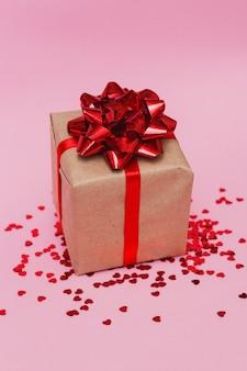 Prezent z czerwoną kokardką i czerwonym konfetti w kształcie serca na różowym stole na walentynki.