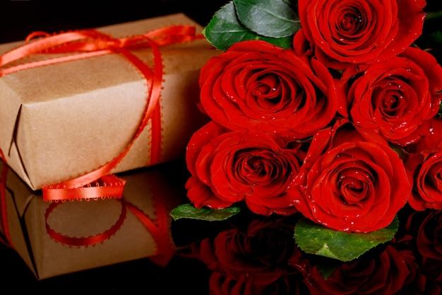 Prezent z czerwoną wstążką i bukietem pięknych czerwonych róż. koncepcja dzień matki lub walentynki.