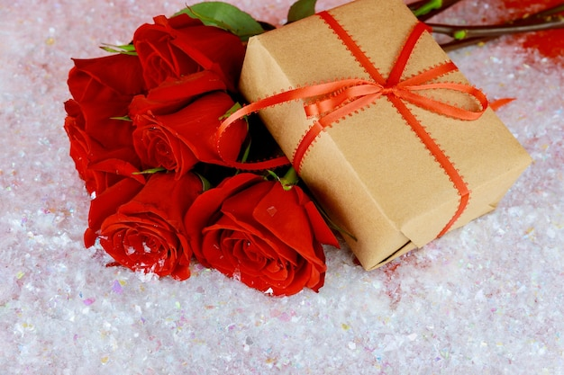 Prezent z czerwoną wstążką i bukietem pięknych czerwonych róż na błyszczącym śniegu.