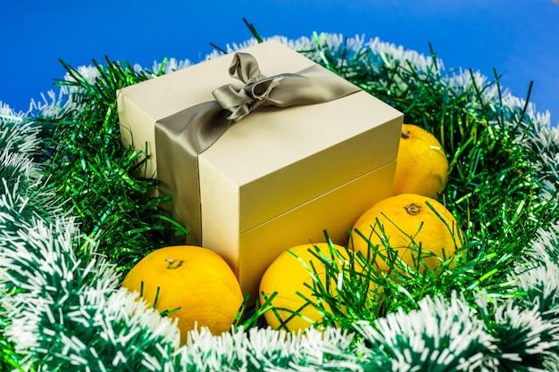 Prezent z kokardą i mandarynkami ciasno owiniętymi zielonym blichtrem na niebieskim tle. dekoracja świąteczna i noworoczna.