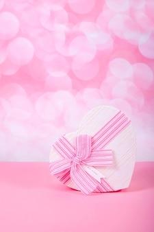 Prezent z kokardą w kształcie serca na różowym tle z bokeh