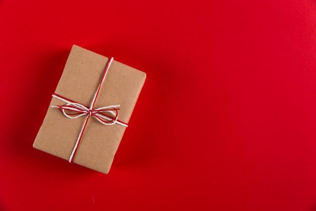 Prezent z papieru rzemieślniczego i lin na czerwonym, boże narodzenie, copyspace.