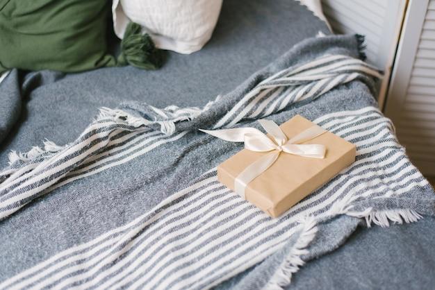 Prezent z papieru rzemieślniczego, przewiązany beżową satynową tasiemką leży na kocu na łóżku