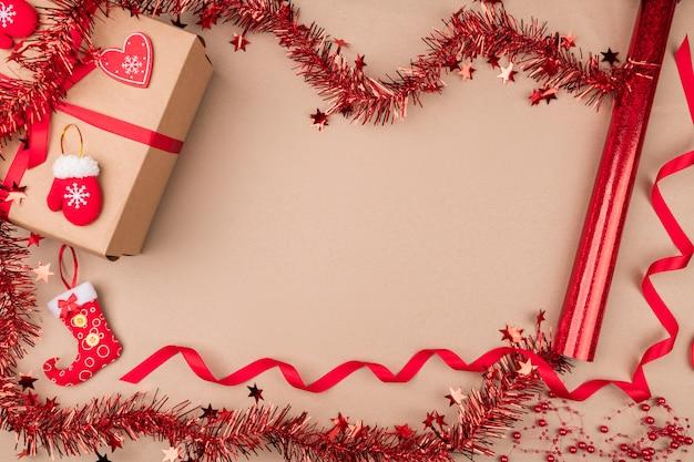 Prezent z papieru rzemieślniczego, umieszczony wśród czerwonego świątecznego blichtru, czerwonej kręconej wstążki, małych ozdobnych mitenek i pończochy na słodycze. nastrój. duch świąt.