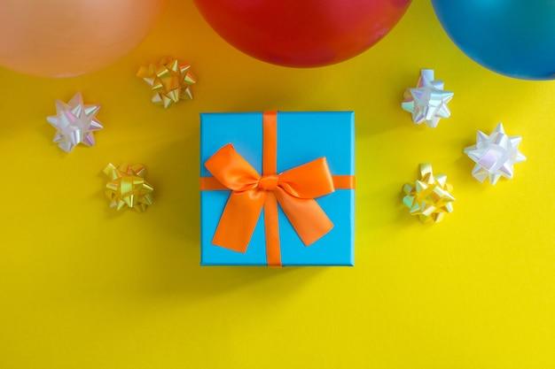 Prezent z pomarańczową kokardką i kolorowe balony na żółtym tle. widok z góry. skopiuj miejsce.