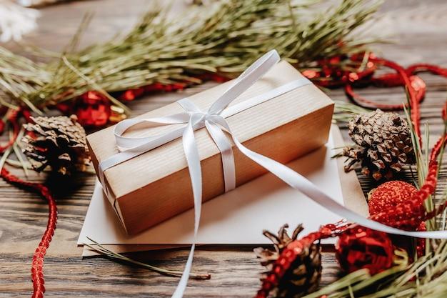 Prezent z pustą notatką z gałęzi jodły i świątecznych zabawek na podłoże drewniane. koncepcja nowego roku