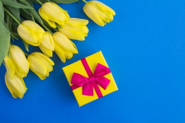 Prezent z różową kokardką i żółtymi tulipanami na niebiesko