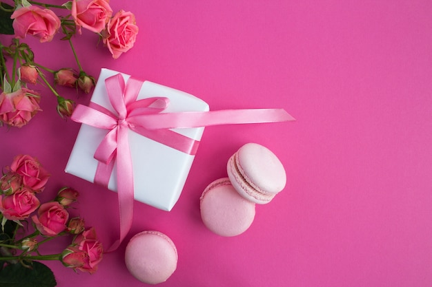 Prezent z różową kokardką, makaronikami i różowymi różami