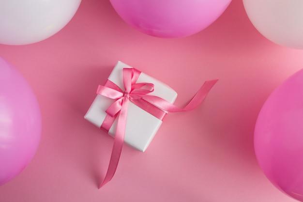 Prezent z różowo-białymi balonami na różowej powierzchni widok z góry.