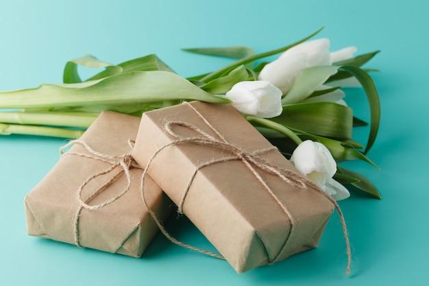 Prezent z wiosennych kwiatów białych tulipanów z prezentami