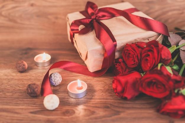 Prezent z zapalonymi świecami i róż