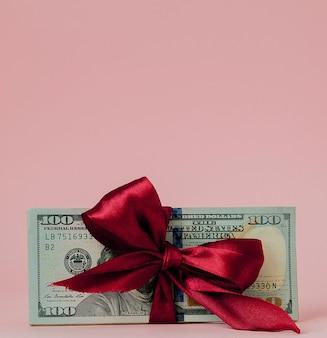 Prezent za sto dolarów owinięty czerwoną wstążką na różowym tle.