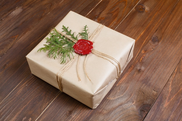 Prezent zapakowany w papier pakowy, wiązany sznurkiem i klejoną woskową pieczęcią. leżąc na stole.