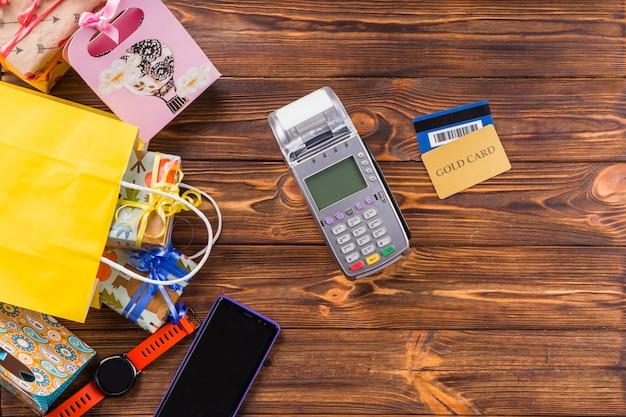 Prezent zapakowany; zegarek na rękę; telefon komórkowy; terminal płatniczy i karta bankowa na drewnianym stole