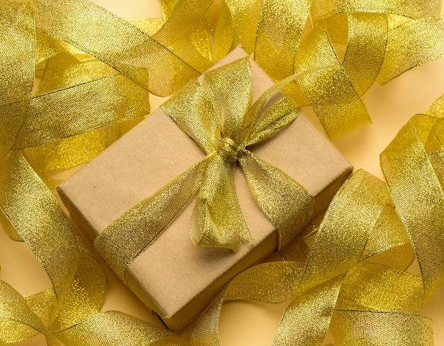 Prezent zawinięty w brązowy papier na powierzchni skręconej złotej wstążki, świąteczna powierzchnia, widok z góry