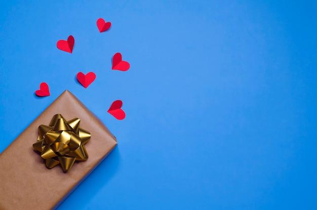 Prezent ze złotą kokardą i czerwonymi sercami jako znak miłości na niebieskim tle na nowy rok, boże narodzenie, walentynki, urodziny.