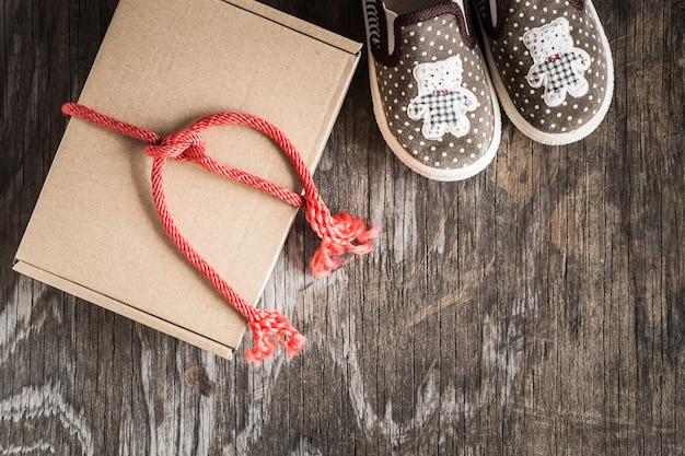 Prezenta pudełko i buty na starym drewno stole, odgórny widok