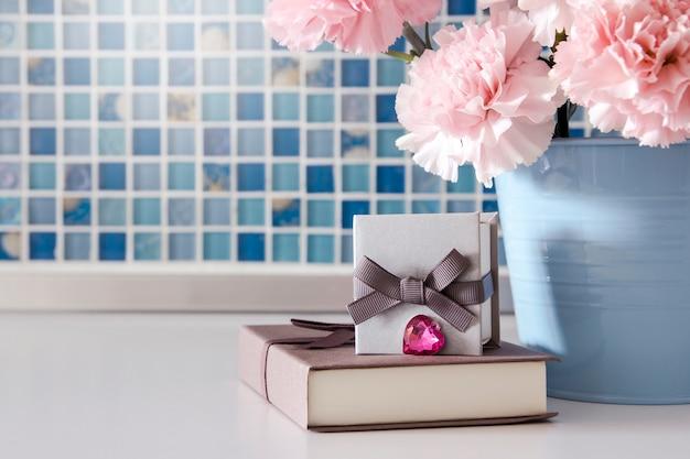 Prezenta pudełko i goździków kwiaty w wiadrze
