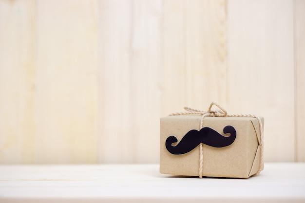 Prezenta pudełko, papierowy wąsy na drewnianym tle z kopii przestrzenią. szczęśliwego dnia ojca.