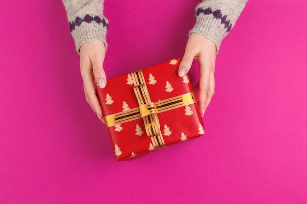 Prezenta pudełko w żeńskich rękach na różowym tle