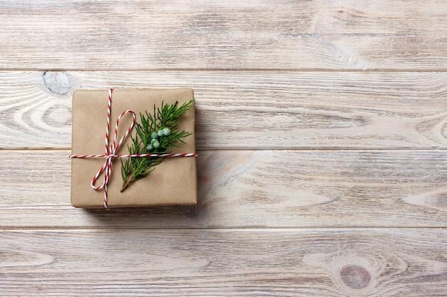 Prezenta pudełko z czerwonym faborkiem nad białym drewnianym tłem