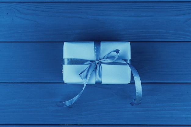 Prezenta pudełko z faborkiem na błękitnym tle, odgórny widok